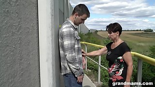Mature woman over 60 gives a blowjob to hot young mendicant outdoor